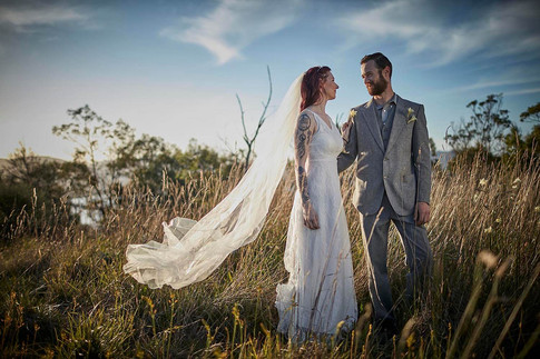 Wedding photography, wilderness elopement Tasmania, couple stands in late afternoon sun in paddock
