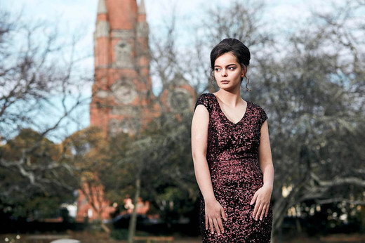Fashion shoot, girl in evening dress at a park
