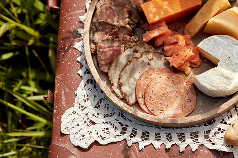 Food photography, charcuterie and cheese platter on a vintage trunk in the garden