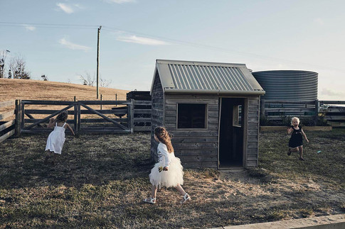 Wedding photography, flower girls play a game in a paddock, late afternoon sun
