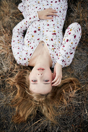 Outdoor portrait, girl in floral dress lies down on grass and looks at camera