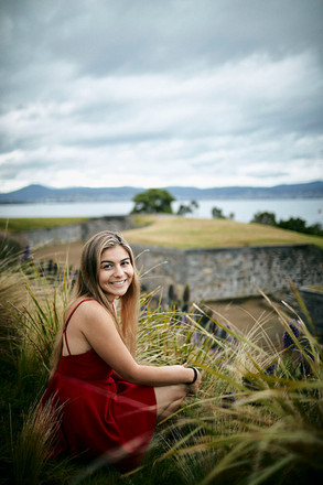Outdoor portrait, girl in red dress sitting in grass at Alexandra Battery, Sandy Bay, Hobart