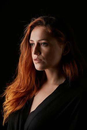 Studio portrait dramatic lighting on redhead girl