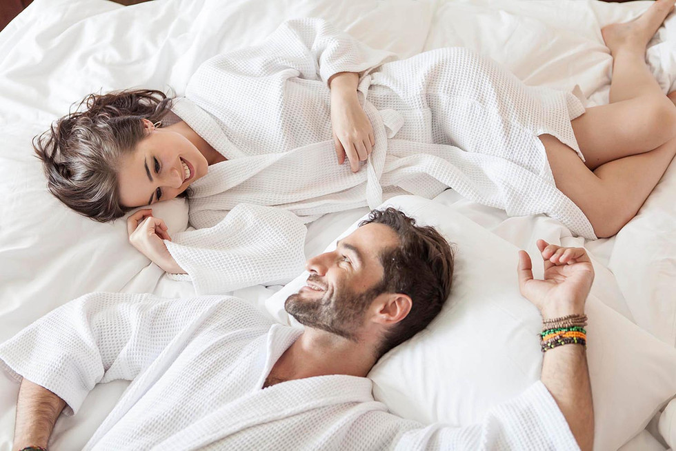 Couple on hotel bed bright morning light