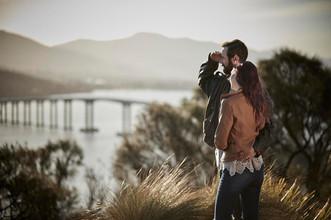 Couple in late afternoon sun overlooking Tasman bridge