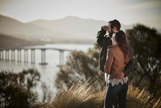 Couple in late afternoon sun overlooking Tasman bridge