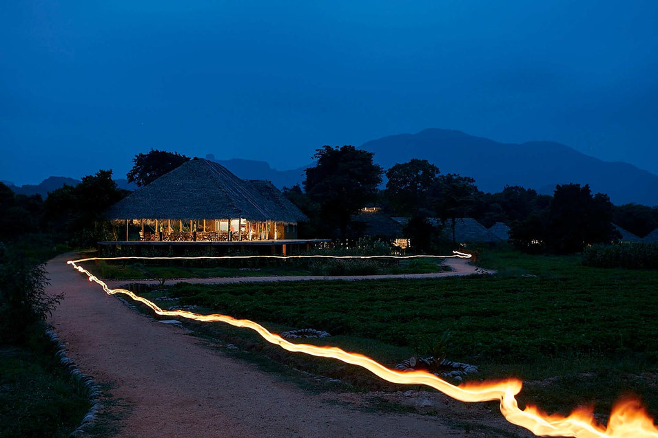 Architectural photography, fire trail on footpath outside a lowland thatched roof hut