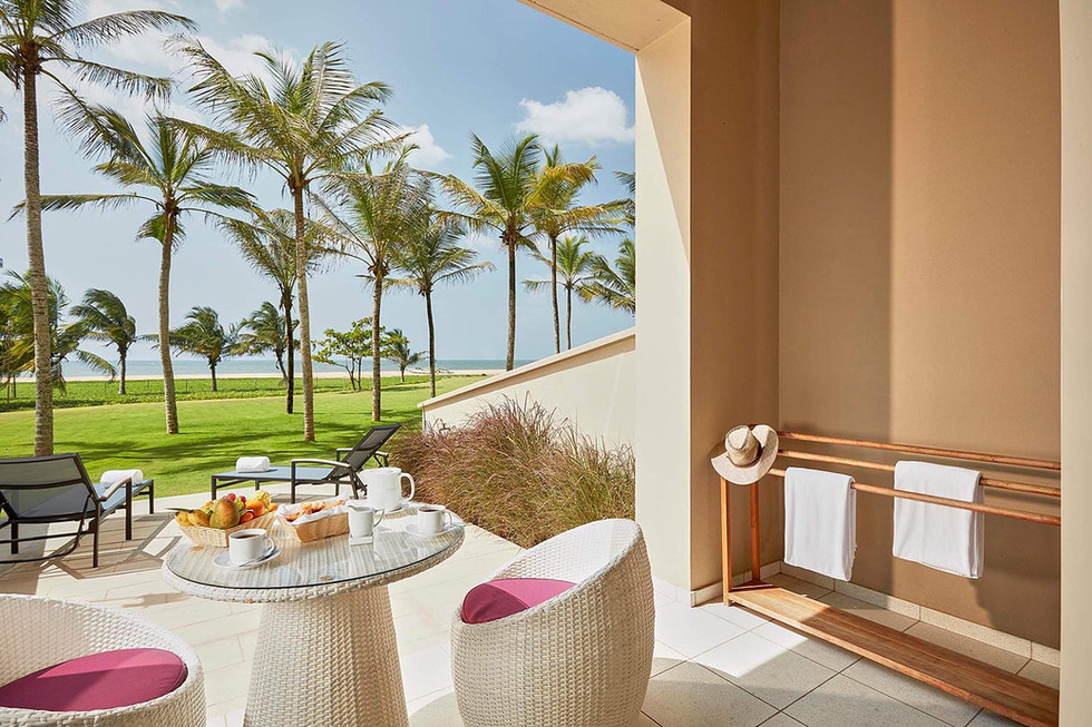 Architectural photography, hotel room exterior deck overlooking palm trees and blue sea