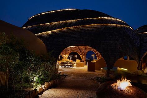Architectural photography, domed safari lodge at dusk. Warm glowing light and blue night sky, Wild Coast, Sri Lanka