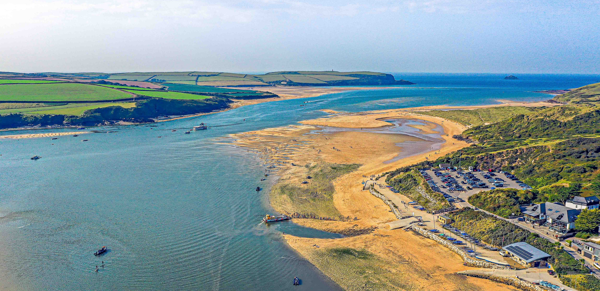 Wadebridge Estuary from the air with a drone. You can see the beaches and river flowing into the sea.