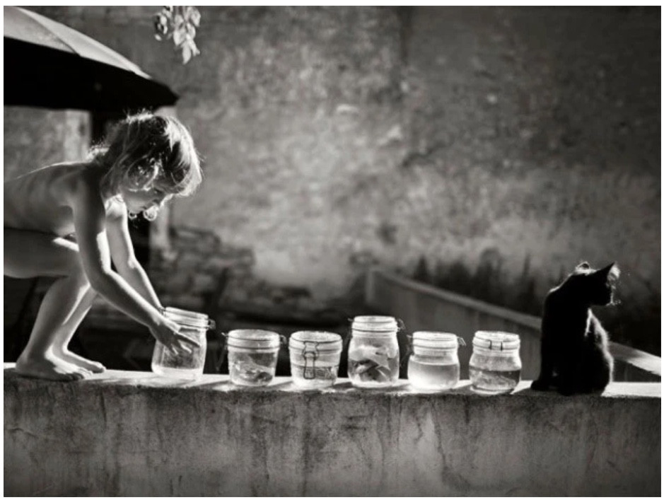 naked child on a fence holding jars of water with cat