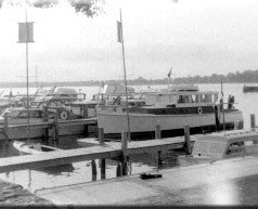 Cabin cruisers at their slips during a weekend in 1957. Mark boats and the committee boat moored at docks in the scene's foreground show the new haulout area completed in time for the 1957 Thistle Class Nationals.