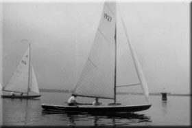 Wooden Star boats returning to the club on a calm day. In the 1930's the boats were moored in front of the club, preceding hoists and two wheel trailers. Some wood vessels needed to 'soak up' and remain in the water.