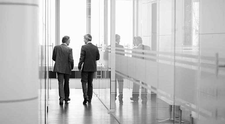 two people walking in an office