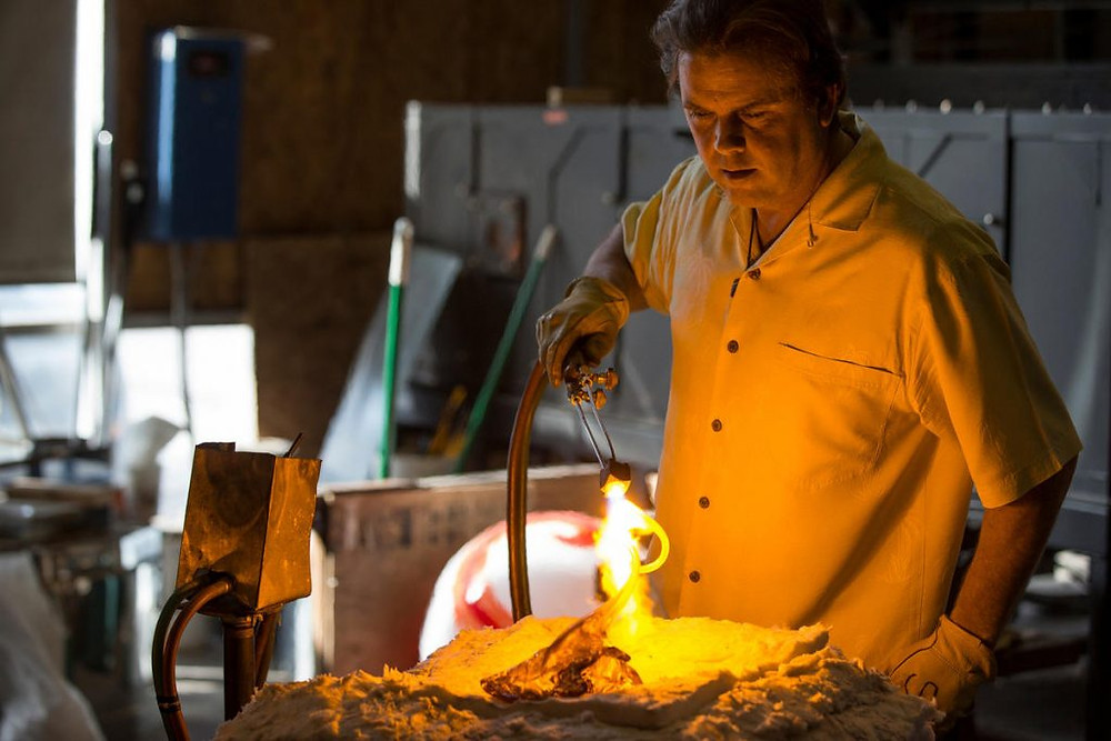 Tom Holdman, a glass blowing artist, creating a glass flower.
