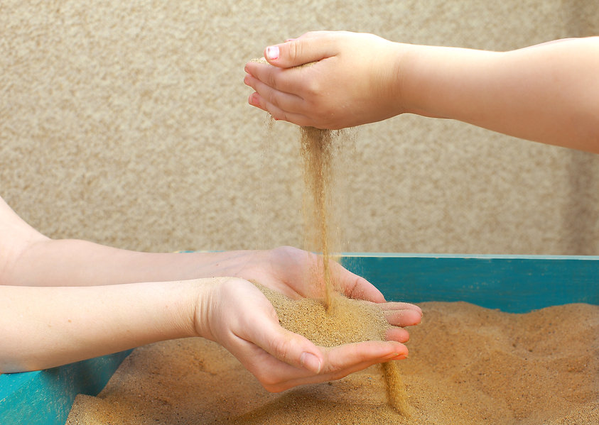sand therapy. Hands adult and child play