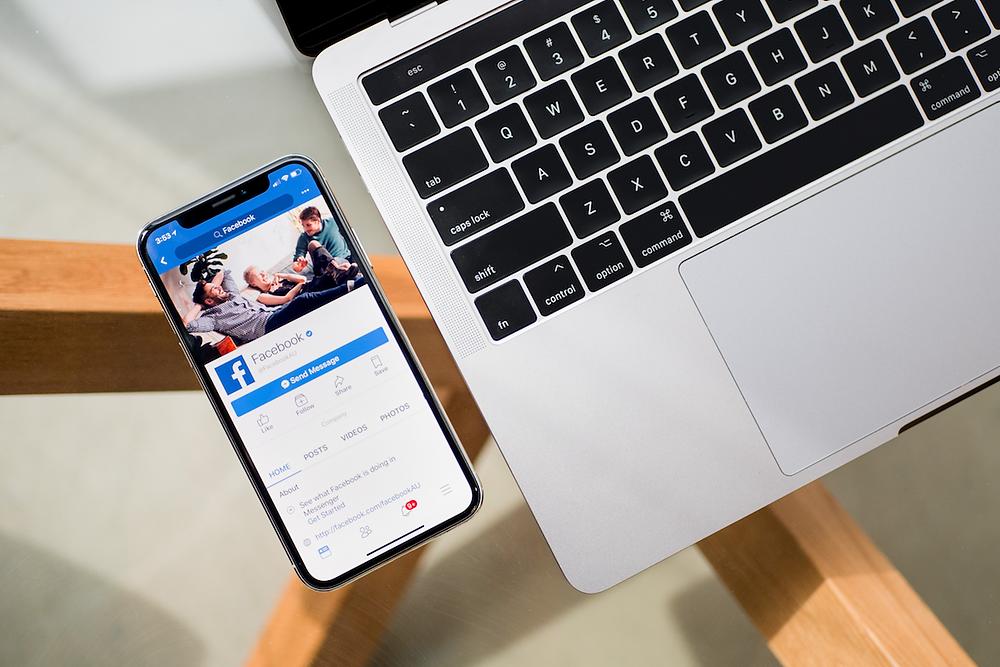Smartphone with Facebook app next to MacBook