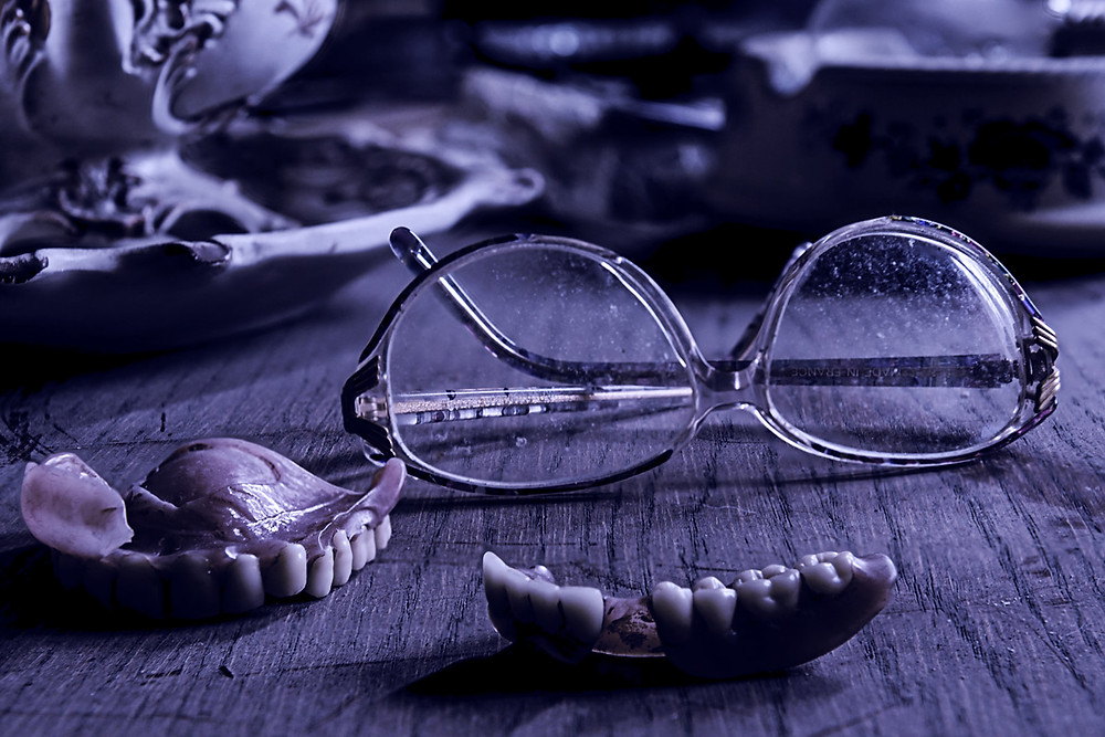 Dentures on table next to eyeglasses