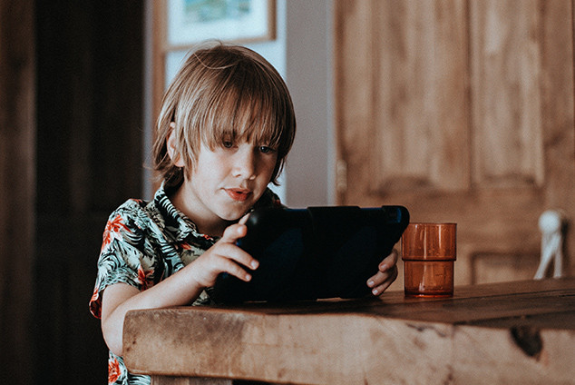 Boy holding tablet at kitchen table