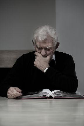 Depressed caregiver with Photo Album needing relief and support