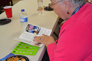 senior lady playing bingo stops to look at Area Agency on Aging brochure to learn about services offered
