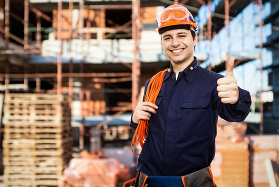 Man with hard hat and thumbs up, warehouse, workshop