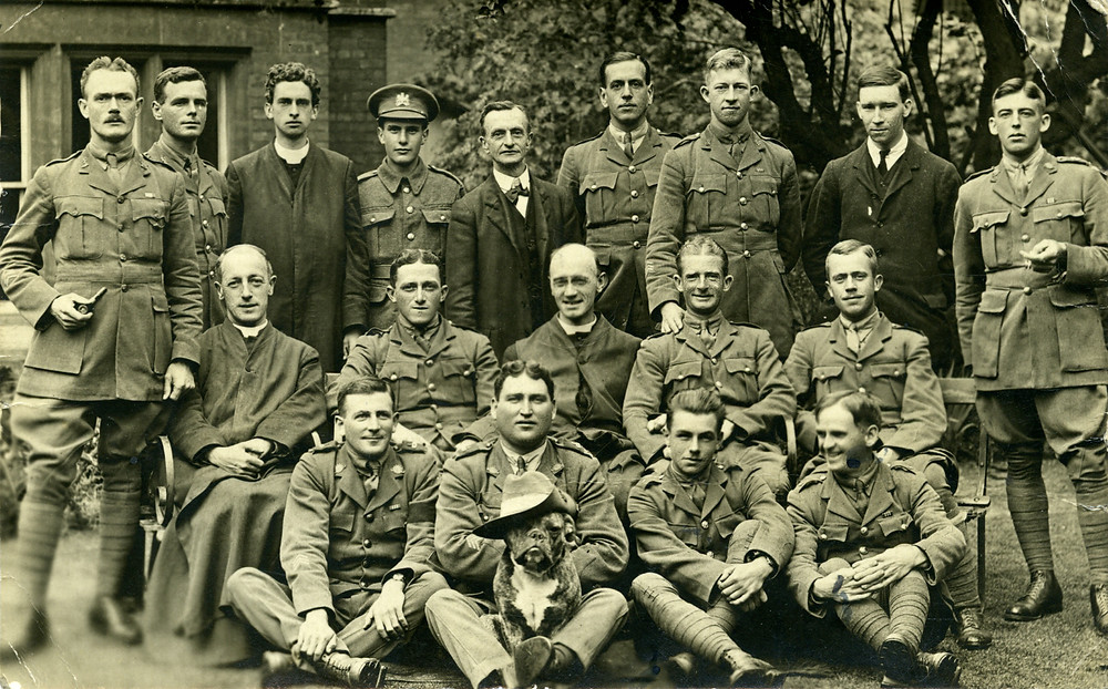 Group of men formerly arranged in 3 rows, mostly in military uniform with 3 in clerical dress and two in suits. At front of group sits a dog with a hat on his head.