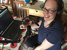 Photo of white woman smiling wearing headphones and looking up from laptop