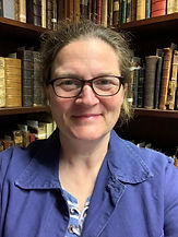Close up profile photo of a white woman smiling with books in background