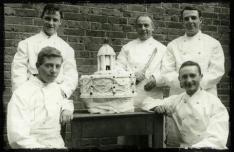 Five men in chefs jackets smiling at photographer grouped around a table on which there is a large fancy decorated cake with a dome temple on top. One man holds a large knife.