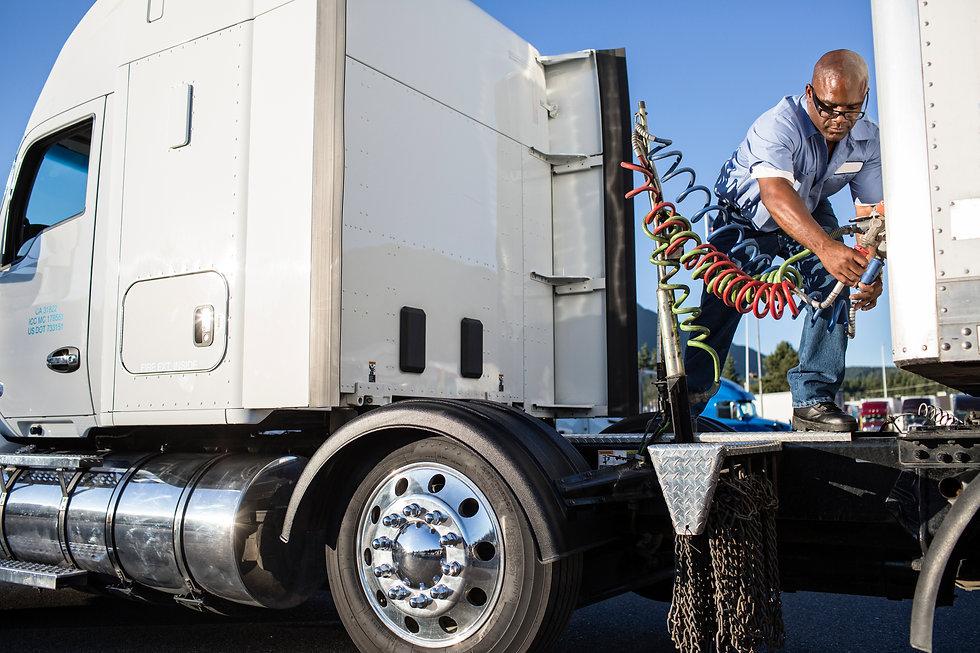 black-man-truck-driver-attaching-power-c