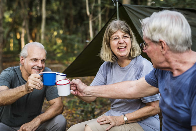 Cheers with coffee mugs while camping