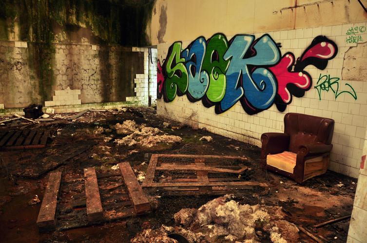 Interior habitación con sillón y palets abandonados