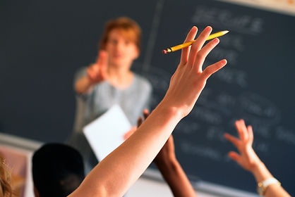 Teacher teaching a class. Raised hand with pencil. Students in the classroom.