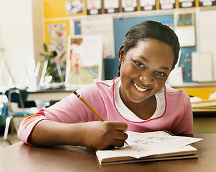 Picture of a smiling girl studying with worksheets