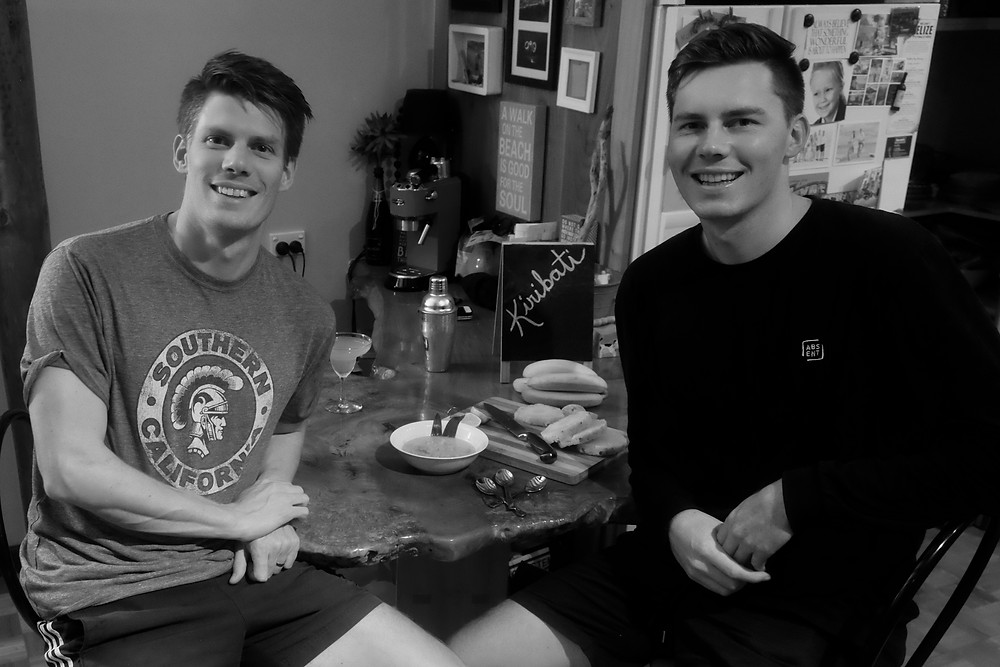 A black and white image of Aaron and his brother, Dan, sharing a meal from Kiribati together.