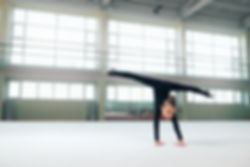 little gymnast standing on hand doing th