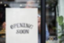 Man putting on store opening soon sign.j