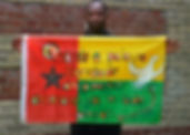 Art warning the World, Guinea Bissau - Braîma Injaî and his flag with the Klaus Guingand sentence in Portuguese / Paint / Signed