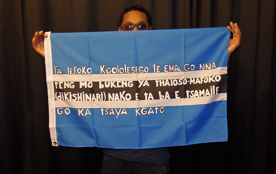 Art warning the World / Botswana - Fenyang and his  flag with the Klaus Guingand sentence  in Setswana.