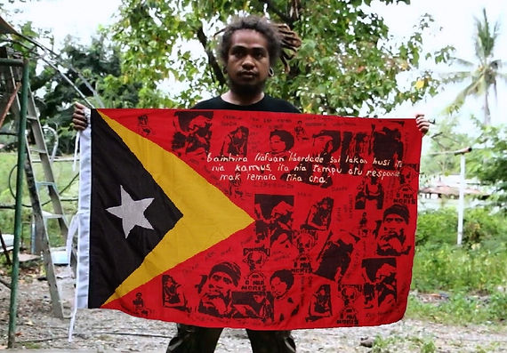 Art warning the World,Timor Leste - Benny Farga and his flag with the Klaus Guingand sentence in Tetum.