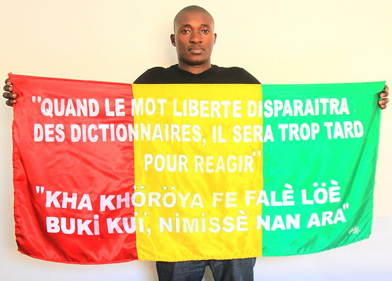 Art warning the World, Guinea - Sivily Koivogui and his flag with the Klaus Guingand sentence in French and Susu /white serigraphy / Signed