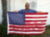 Art warning the World, United States -Marcus Jansen andhis flag with the Klaus Guingand sentence in American/ Flag: 35,5 x 59 in./ Sentence red stencil / Signed