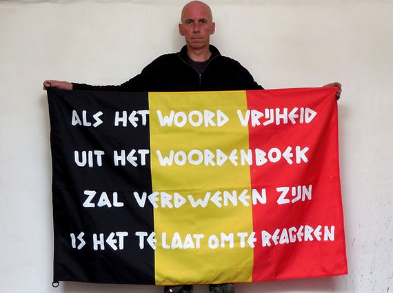 Art warning the World, Belgium (Flanders) - Werner Pans and his flag with the Klaus Guingand sentence in Flemish / White paint / Signed