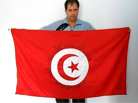 Art warning the World,Tunisia - Majed Zalila and his flag with the Klaus Guingand sentence in Arabic.