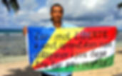 Art warning the World, Seychelles - George Camille and his flag with the Klaus Guingand sentence in Seychellois Creole / Flag: 31,5 x 43 in/ Sentence Black paint / Signed