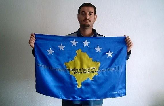 Art warning the world, Kosovo - Kushtrim Zeqiri and his flag: 23 x 35,4 inches / Klaus Guingand sentence in Albanian / Black & white paint / Signed