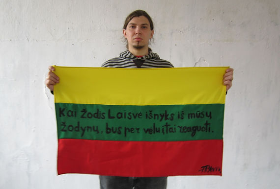 Art warning the World, Lithuania -  Povilas Ramanauskas and his flag with the Klaus Guingand sentence in Lithuanian / Flag: 23 x 35,4 in./ Sentence black marker pen / Signed