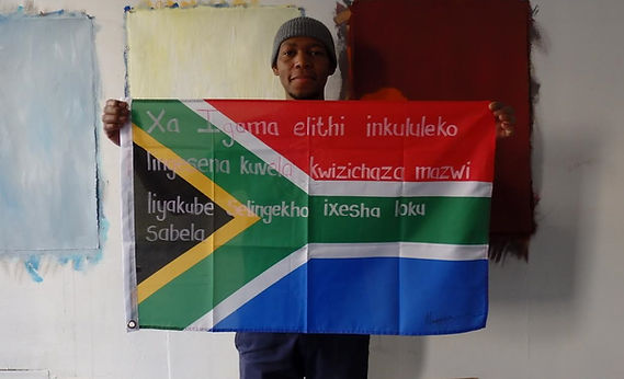 Art warning the World, South Africa (Xhosa)- ​Mongezi Ncaphayi and his flag with the Klaus Guingand sentence in Xhosa / Flag: 23 x 35,4 in. / Sentence pink paint & white marker / Signed