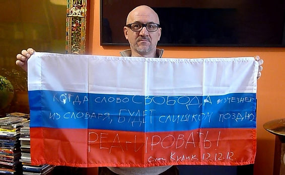 Art warning the World, Russia - Oleg Kulik and his flag with the Klaus Guingand sentence in Russian / Flag: 17,71 x 41,33 in. / Sentence white marker pen / Signed